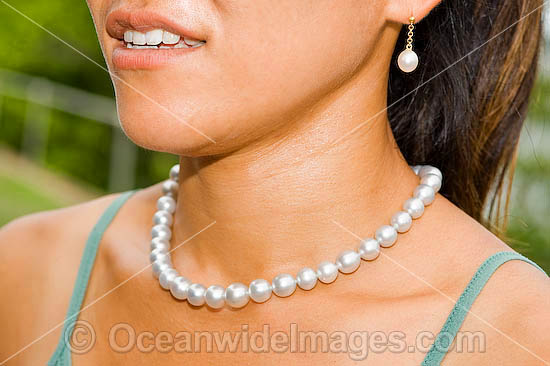 Woman wearing a string of spectacular cultured pearls collected from live Pearl Oyster (Pinctada maxima) at Kazu Pearl Farm. Friday Island, Torres Strait, Queensland, Australia