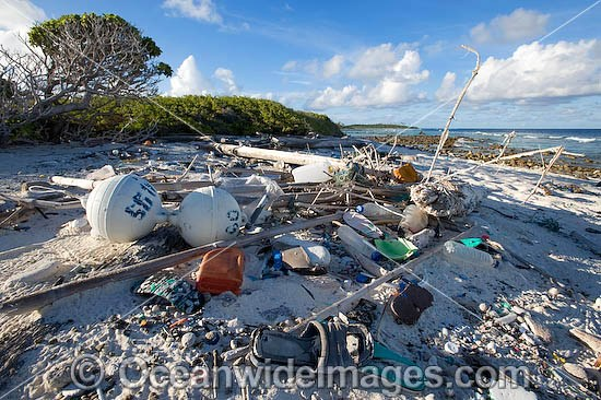 Marine pollution rubbish trash garbage comprising of plastic bottles, footwear and fishing implements washed ashore by tidal movement on a remote tropical island beach - probably drifting in from Indonesia. Cocos (Keeling) Islands, Indian Ocean, Australia Photo - Gary Bell