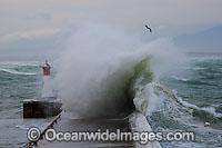 Wave breaking over lighthouse photo