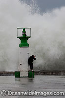 Wave breaking over lighthouse Photo - Chris and Monique Fallows