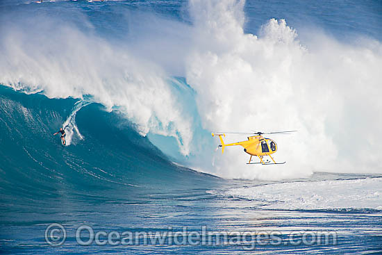 A helicopter filming a tow-in surfer at Peahi (Jaws) off Maui. Hawaii, Pacific Ocean. Photo - David Fleetham