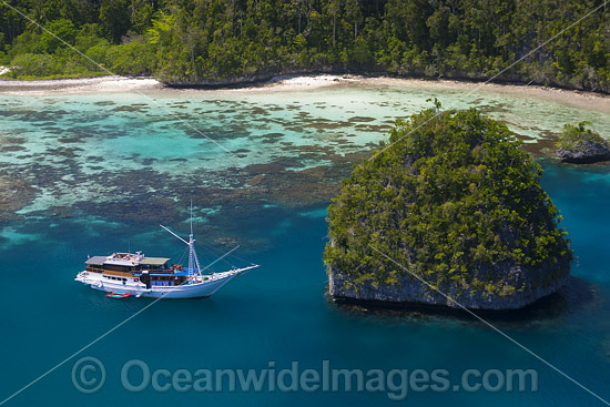 Bugis schooner, used as a live-aboard dive vessel, at anchor in a limestone island lagoon. Uranie Island, Raja Ampat, West Papua, Indonesia. Photo - David Fleetham