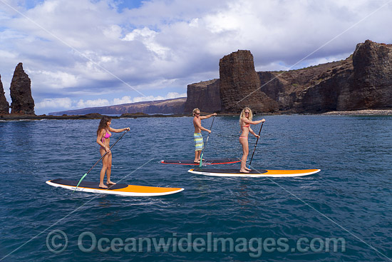 Three young people on stand-up paddle boards at Needles off the island of Lanai, Hawaii. Photo - David Fleetham